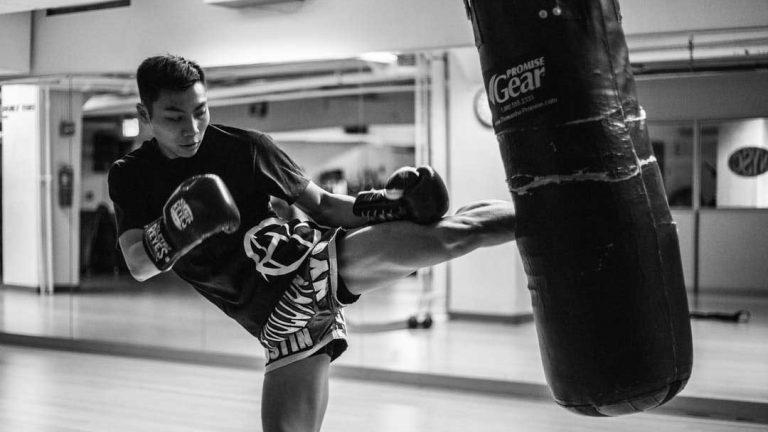Kickboxer man kicking a bag