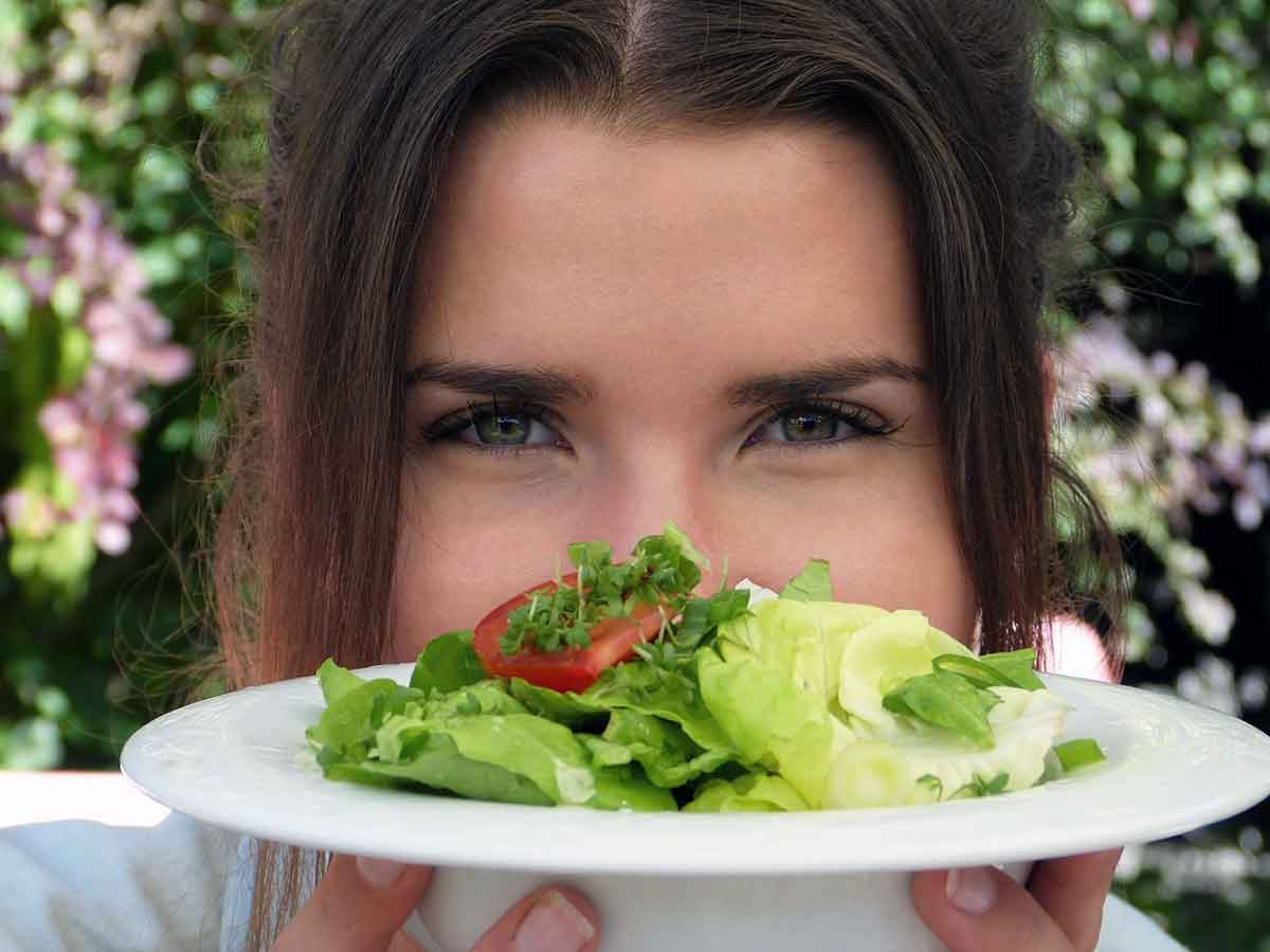 Lady holding a plate of salad