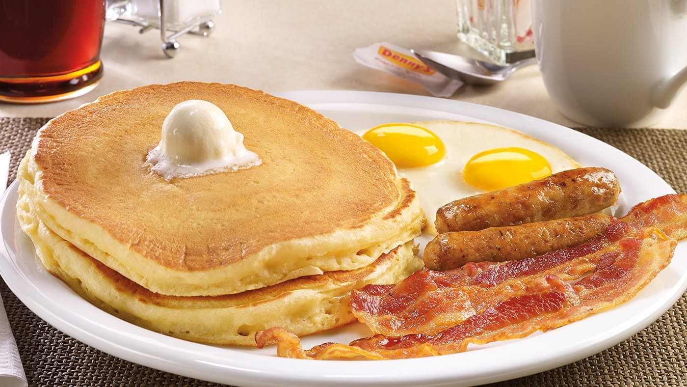 Denny's Grand Slam Breakfast plates with pancakes, eggs, bacon, and sausages.